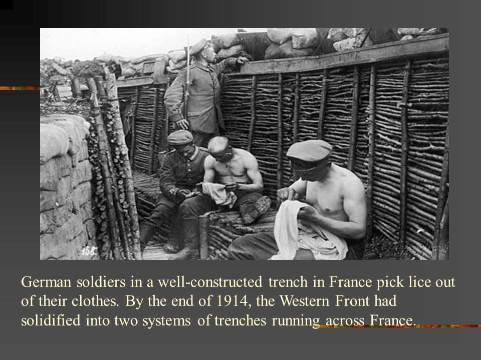 German soldiers in a well-constructed trench in France pick lice out of their clothes.
