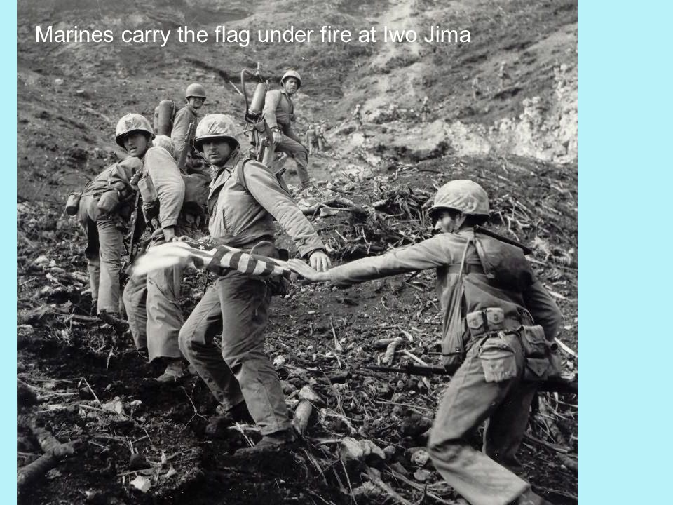 Marines carry the flag under fire at Iwo Jima