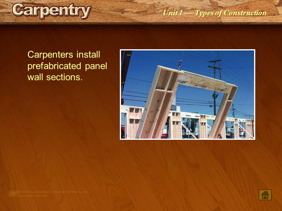 Carpenters install prefabricated panel wall sections.